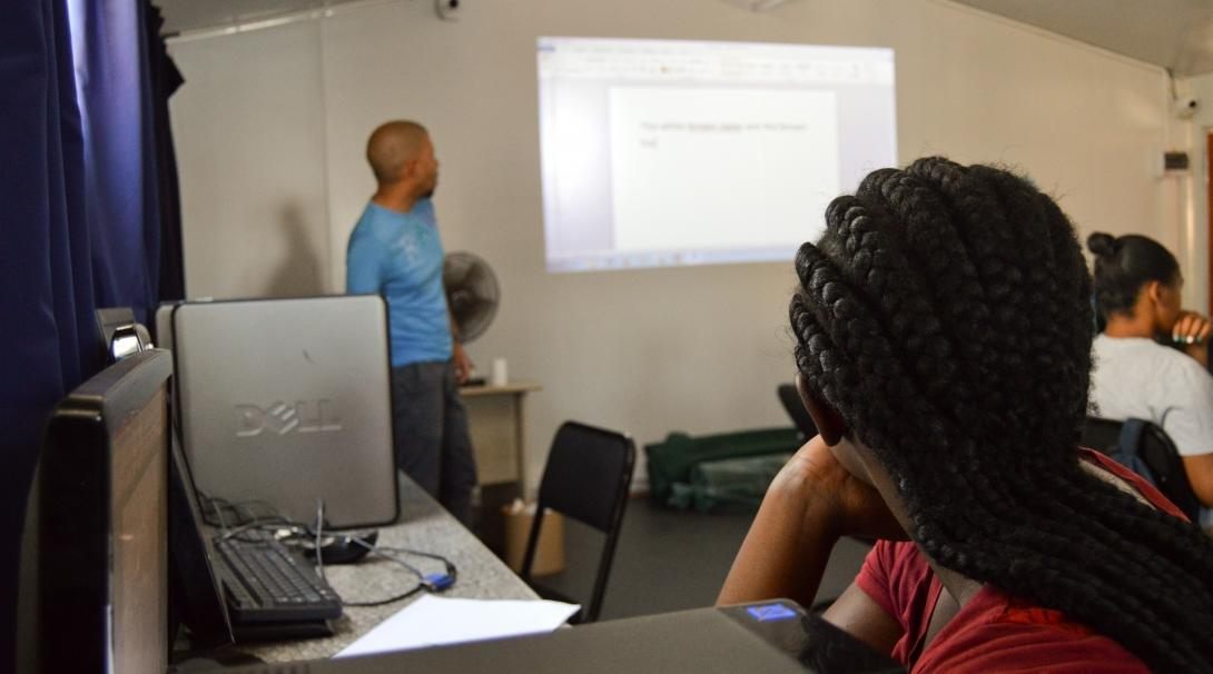 Estudiante recibiendo una clase de informática de nuestro voluntario en Sudáfrica.